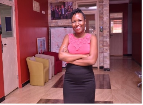 a person wearing their hair up, in a pink tshirt and black skirt stands in the middle of a work space