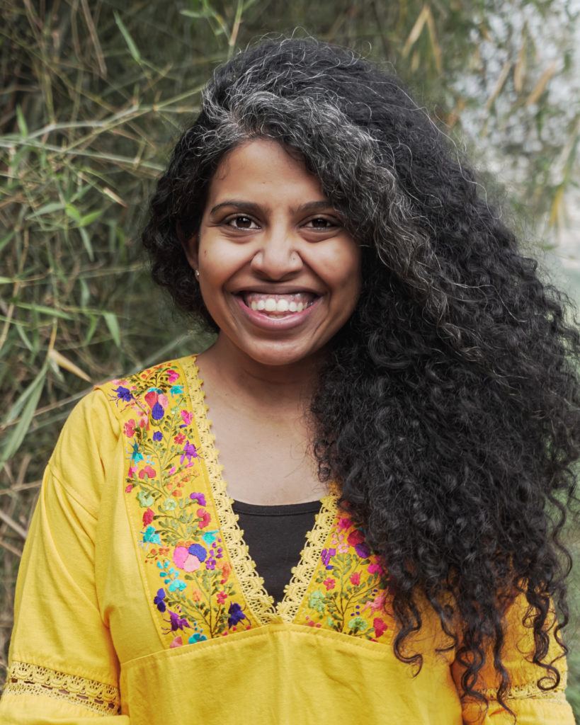 a person with curly black hair is wearing a colourful yellow floral embroidered shirt and smiling