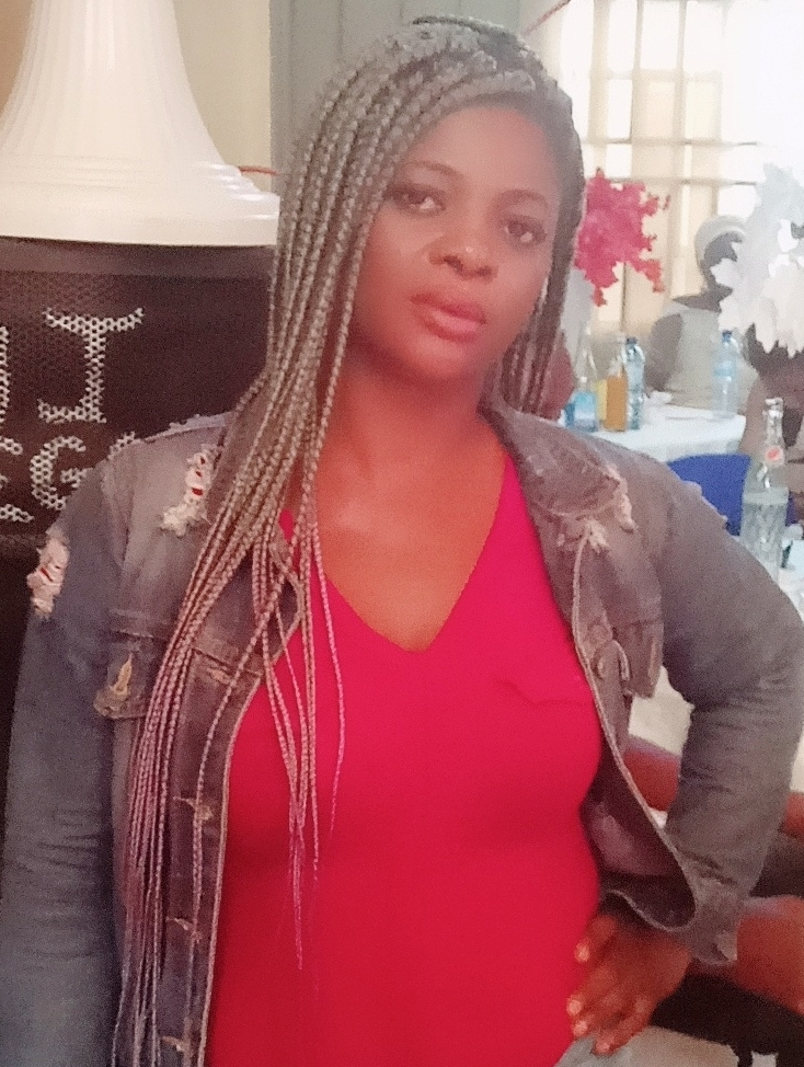 A person is wearing long braids, a red tshirt and denim jacket