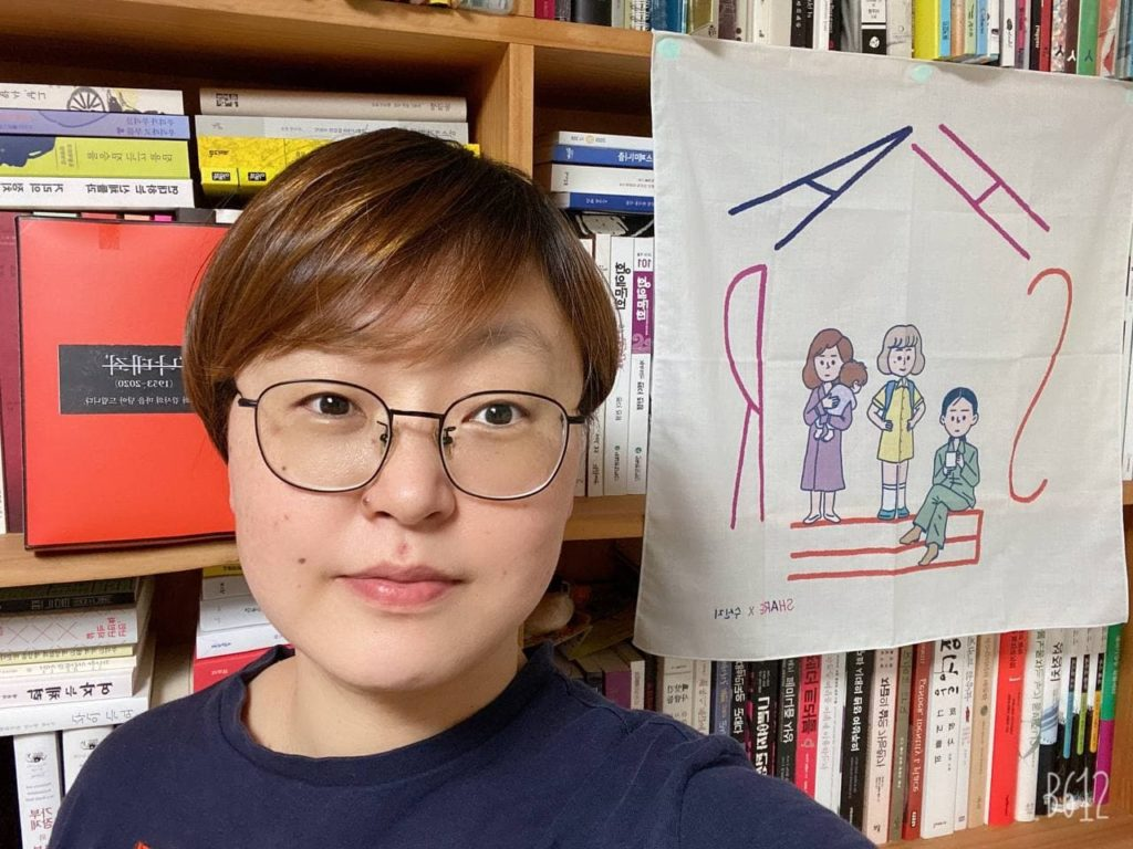 A person wearing spectacles and short brown hair with bangs, stares into the camera. In the background is a bookshelf and a handmade drawing with the acronym SHARE.