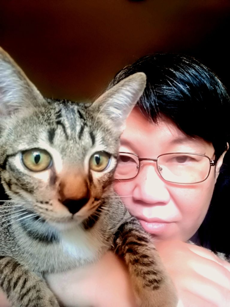 A person wearing spectacles and short black hair peers at the camera alongside their grey-black cat.