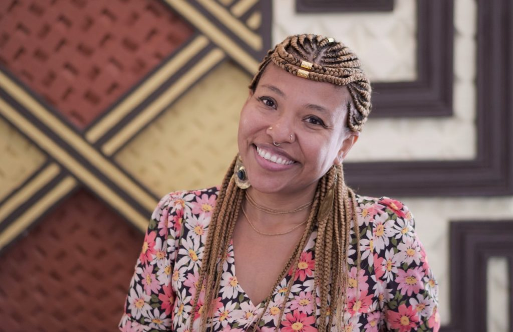 a black woman with long golden braids and beads, wearing a floral blouse shares a beaming smile against a patterned wall mural