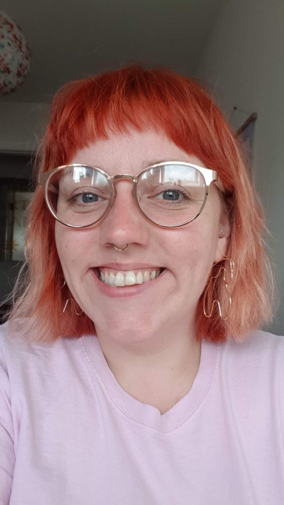 A person wearing gold rimmed spectacles, metallic earrings, a pink tshirt and red hair smiles at the camera