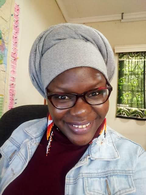 A person wearing a douk, black rimmed spectacles, beaded earrings, a denim jacket and maroon polo neck smiles for the cqmera