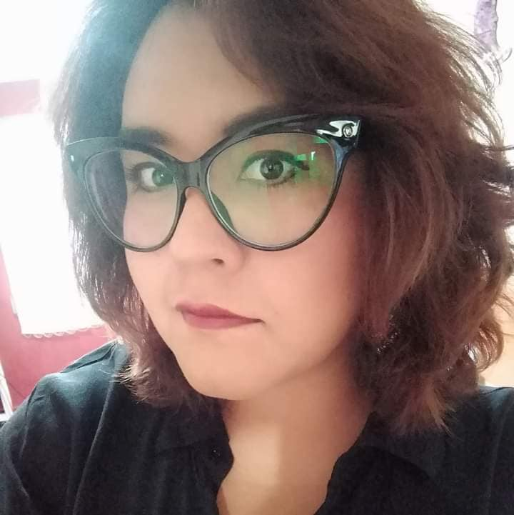 A person wearing large rimmed spectacles, lipstick and a black top glances at the camera